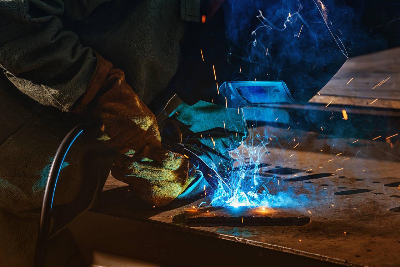 Welder using torch on steel