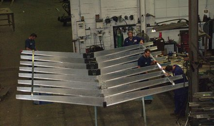 Four men attaching pieces of steel fabricated Starbucks canopy