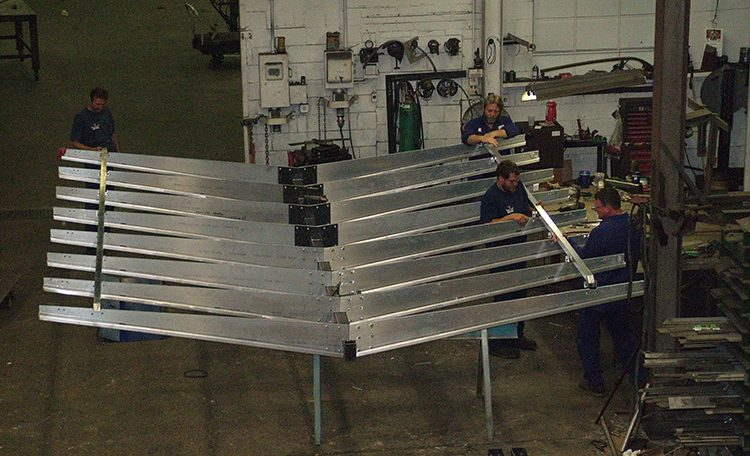 Four men attaching parts to steel fabricated Starbucks canopy