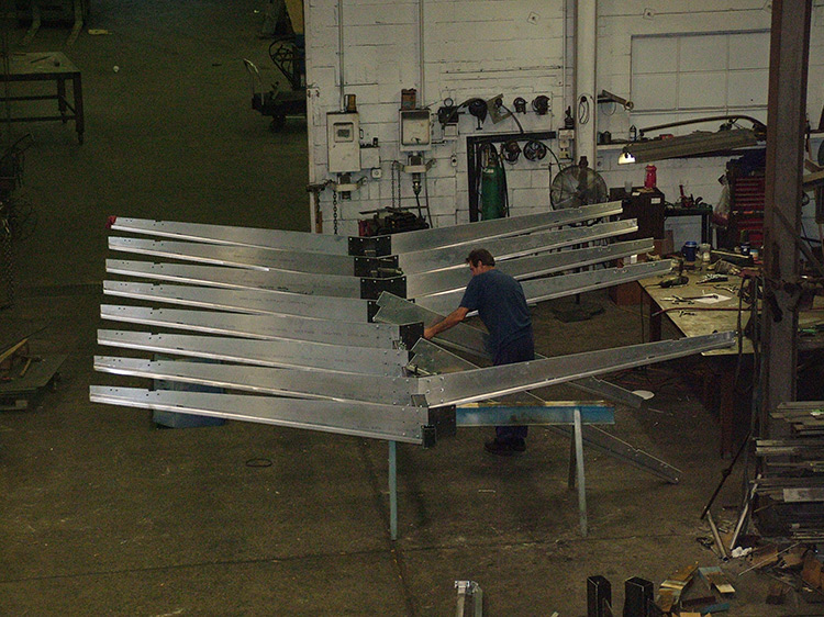 Man attaching parts to steel fabricated Starbucks canopy