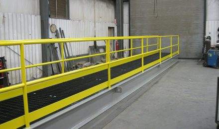 Yellow painted custom steel fabricated platform bridge left angle view