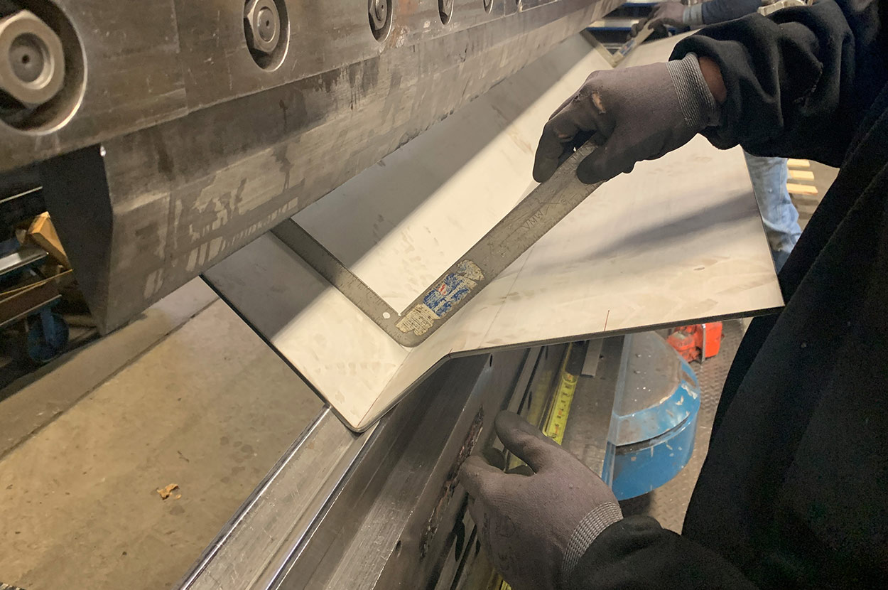 Press brake worker measuring angle of metal fold