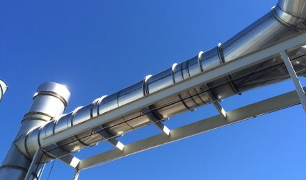 Stainless steel flanged duct against blue sky